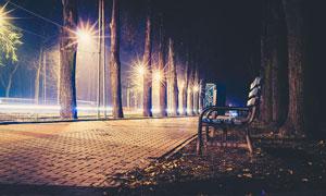夜晚在人行道边的长椅摄影高清图片