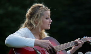 在专心弹奏吉他的美女摄影高清图片