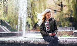 在喷泉边玩手机的美女摄影高清图片