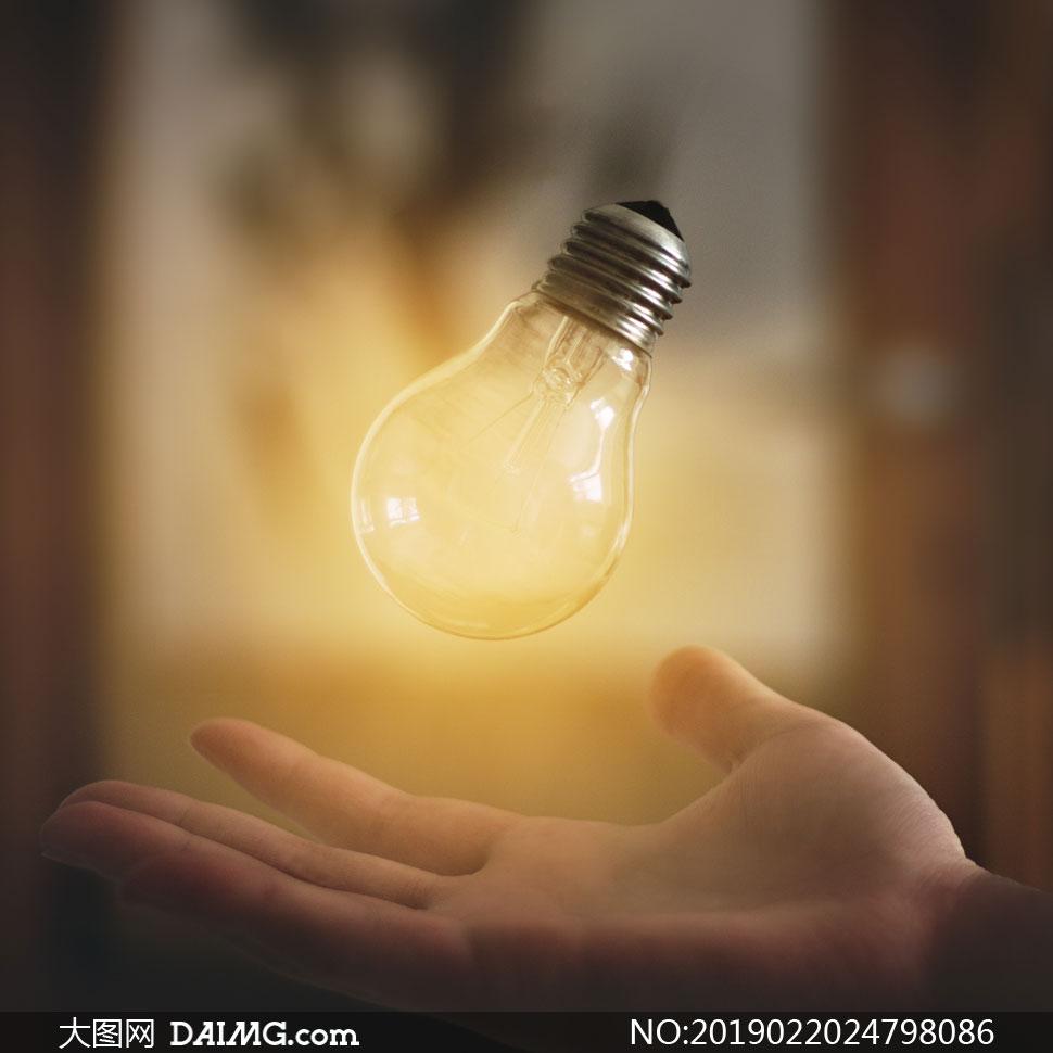 悬浮在掌心上方的灯泡创意高清图片
