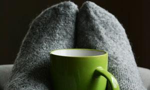 雙腳夾著的綠色馬克杯攝影高清圖片