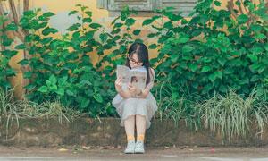 坐在大路邊看書的美女攝影高清圖片