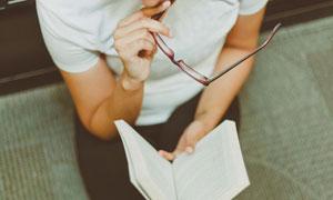 摘掉眼镜思考的阅读者摄影高清图片