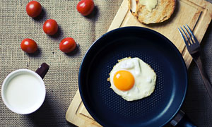 咖啡牛奶與鍋中的煎蛋攝影高清圖片