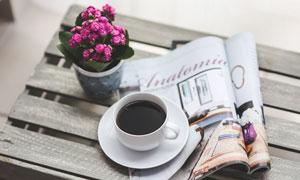 长凳上的咖啡杯与杂志鲜花高清图片