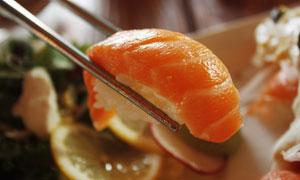 用筷子夹起来的三文鱼寿司高清图片