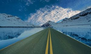 横穿过湖泊通往大山的公路高清图片
