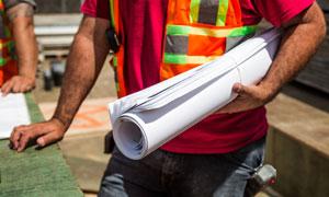 用单手抱着图纸的工人摄影高清图片