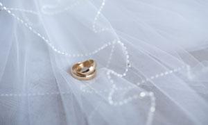 白色婚纱上的结婚戒指摄影高清图片
