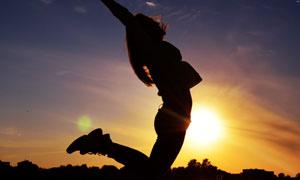 落日余暉下的跳躍人物剪影高清圖片