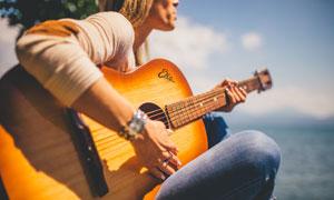 坐在海边弹吉他的人物摄影高清图片