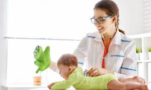 边安抚着婴儿边查体的美女医生图片