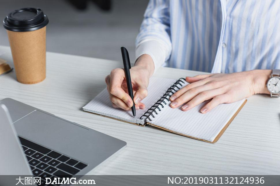 桌面写着字的人物特写摄影高清图片