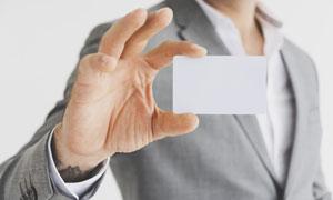 在灰色西装人物手中的卡片高清图片