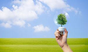蓝天白云草地与手中的灯泡创意图片
