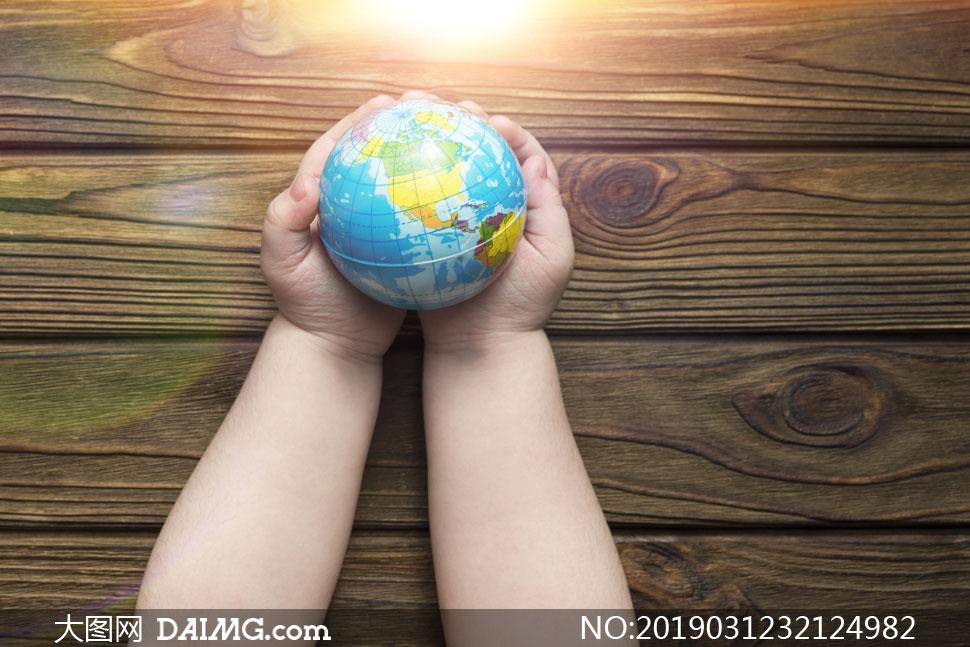 一双胖手里的地球模型摄影高清图片