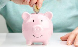放硬币进存钱罐的情景特写高清图片