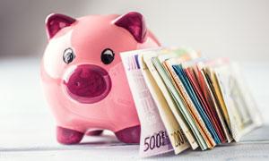 小猪存钱罐与一沓钞票摄影高清图片