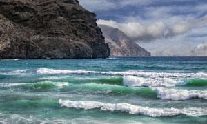 天空山石与涌向海边的波浪高清图片