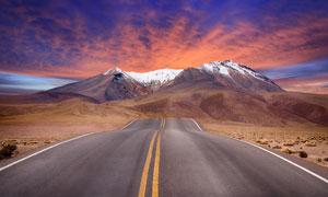 晚霞下通往雪山的公路摄影高清图片