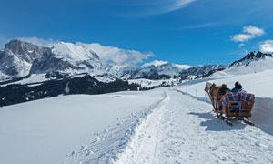 蓝天白云雪山与观光的游客高清图片