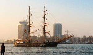 城市建筑物与高桅杆的船只高清图片