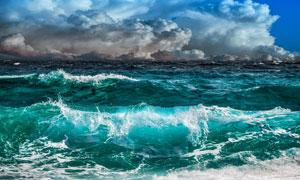 多云天空与波涛澎湃的大海高清图片