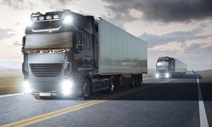 公路上亮着灯的大货车摄影高清图片