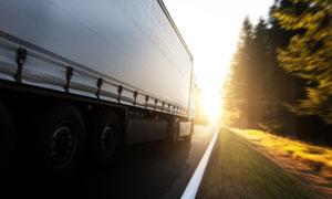 飞驰在路上的货车逆光摄影高清图片