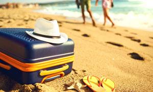 沙滩上的凉鞋行李箱与帽子高清图片