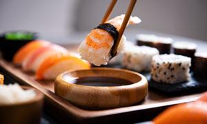 夹着寿司蘸酱料的情景特写高清图片