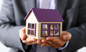 捧在掌心里的紫色房子模型高清图片