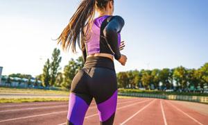 操场跑道上的跑步美女摄影高清图片