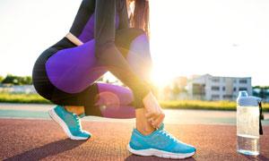 在跑道上系鞋带的美女摄影高清图片