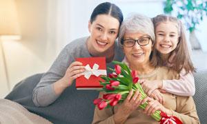 老人小孩与拿礼物盒的美女高清图片