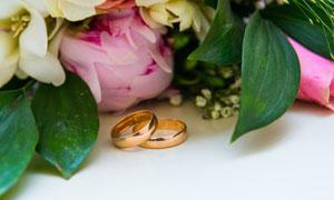 放在鲜花旁的结婚戒指摄影高清图片
