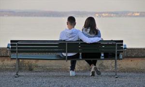坐长椅上看风景的情侣男女高清图片