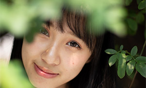 树叶掩映下的微笑美女摄影原片素材