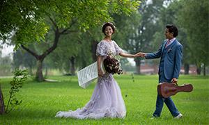 草地上手牵着手的人物婚纱原片素材