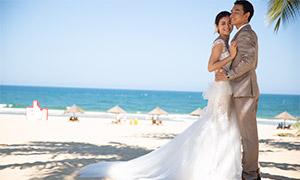 在沙滩上拍摄婚纱照的恋人原片素材