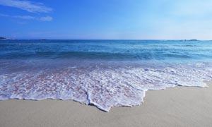 蓝天下的沙滩和海浪摄影图片