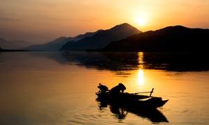 清晨湖邊正在打漁的漁民攝影圖片