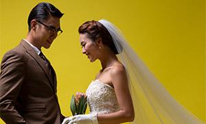 在黄色背景布前的恋人婚纱原片素材