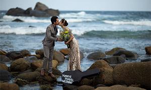 海边礁石上亲吻的男女婚纱原片素材