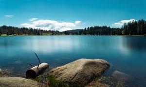 平静的湖泊和岩石摄影图片