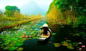 山间划着小舟的农民摄影图片