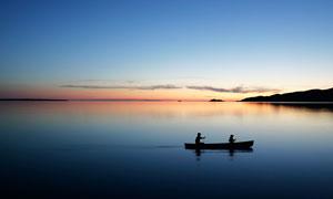 夕陽下在湖中滑行的小舟攝影圖片