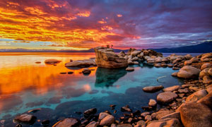 夕阳下的岩石和湖泊美景摄影图片