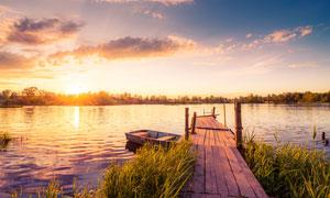 夕陽下的湖邊棧橋和小舟攝影圖片