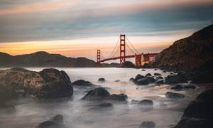 遠景橋梁和河邊巖石攝影圖片